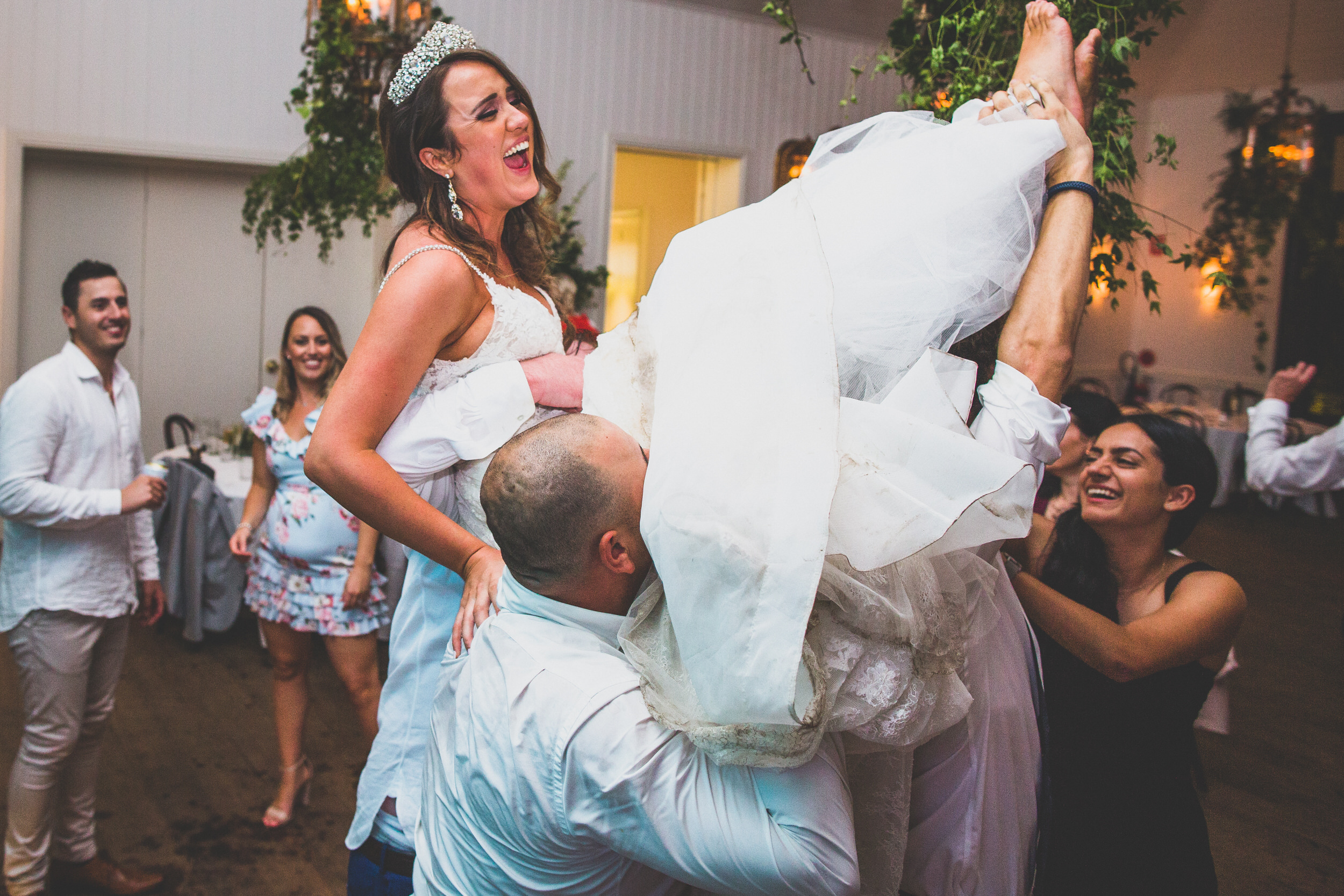 Wedding guests lift the bride and walk around with her!