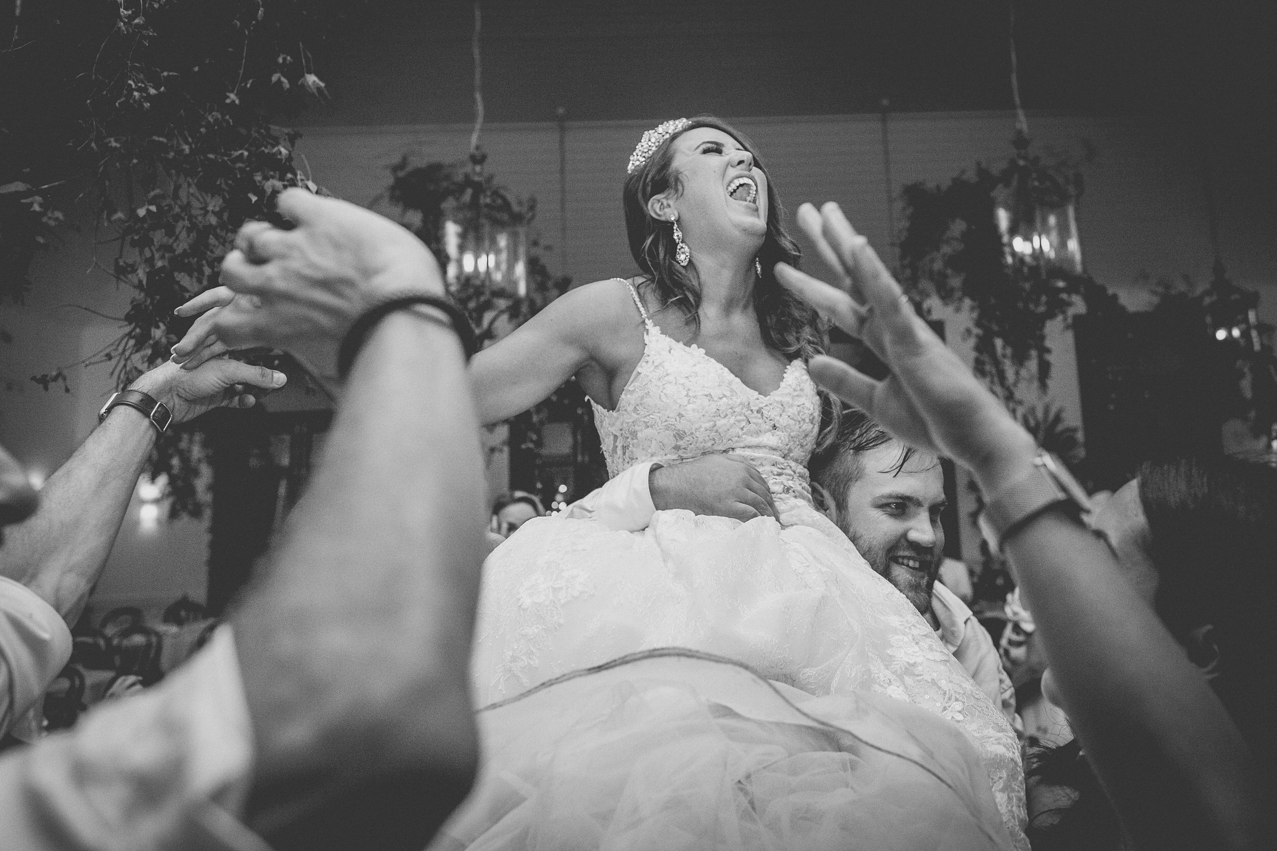 The brides brother lifts her up with everyone cheering around her