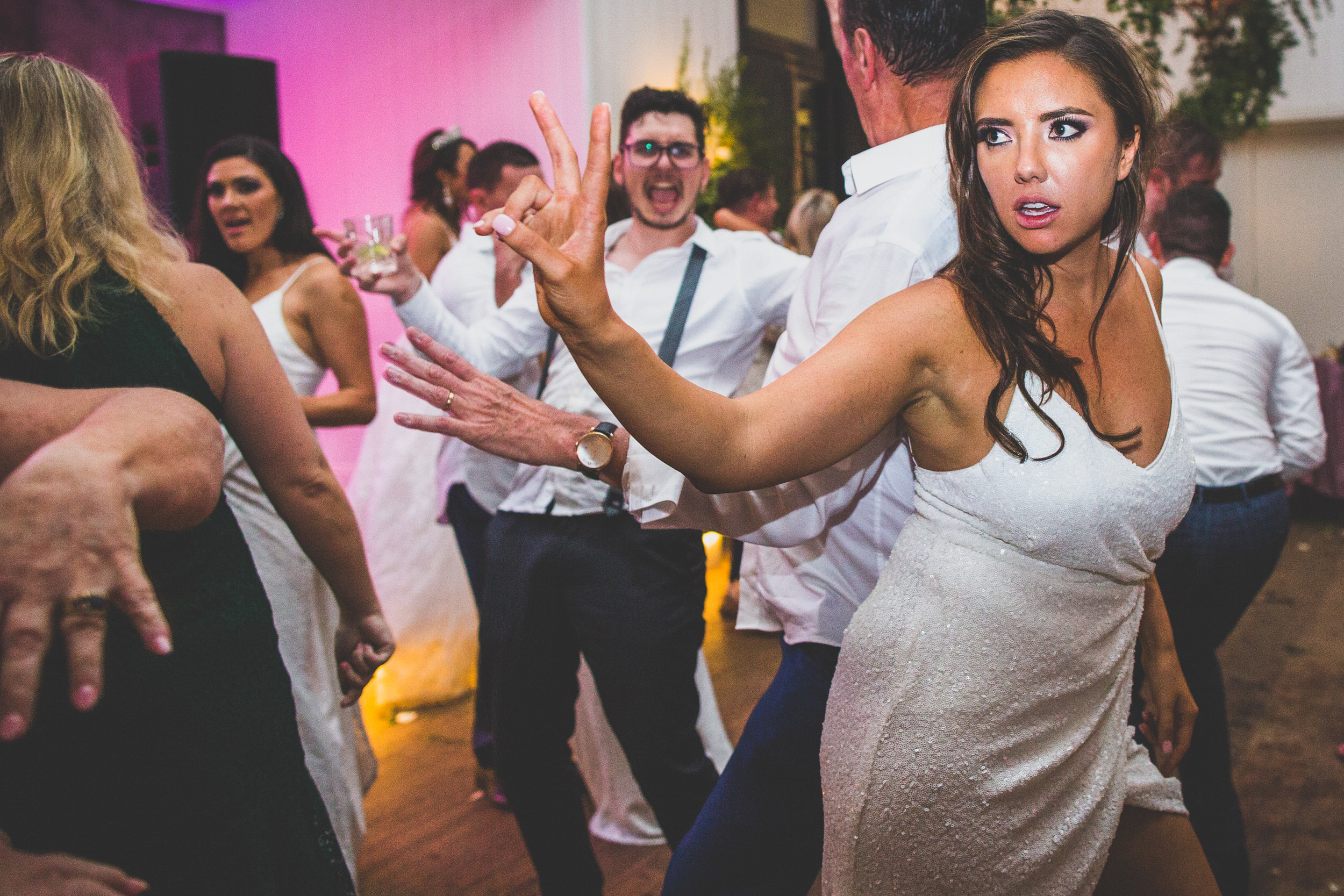 a bridesmaid showing the peace sign on the dance floor