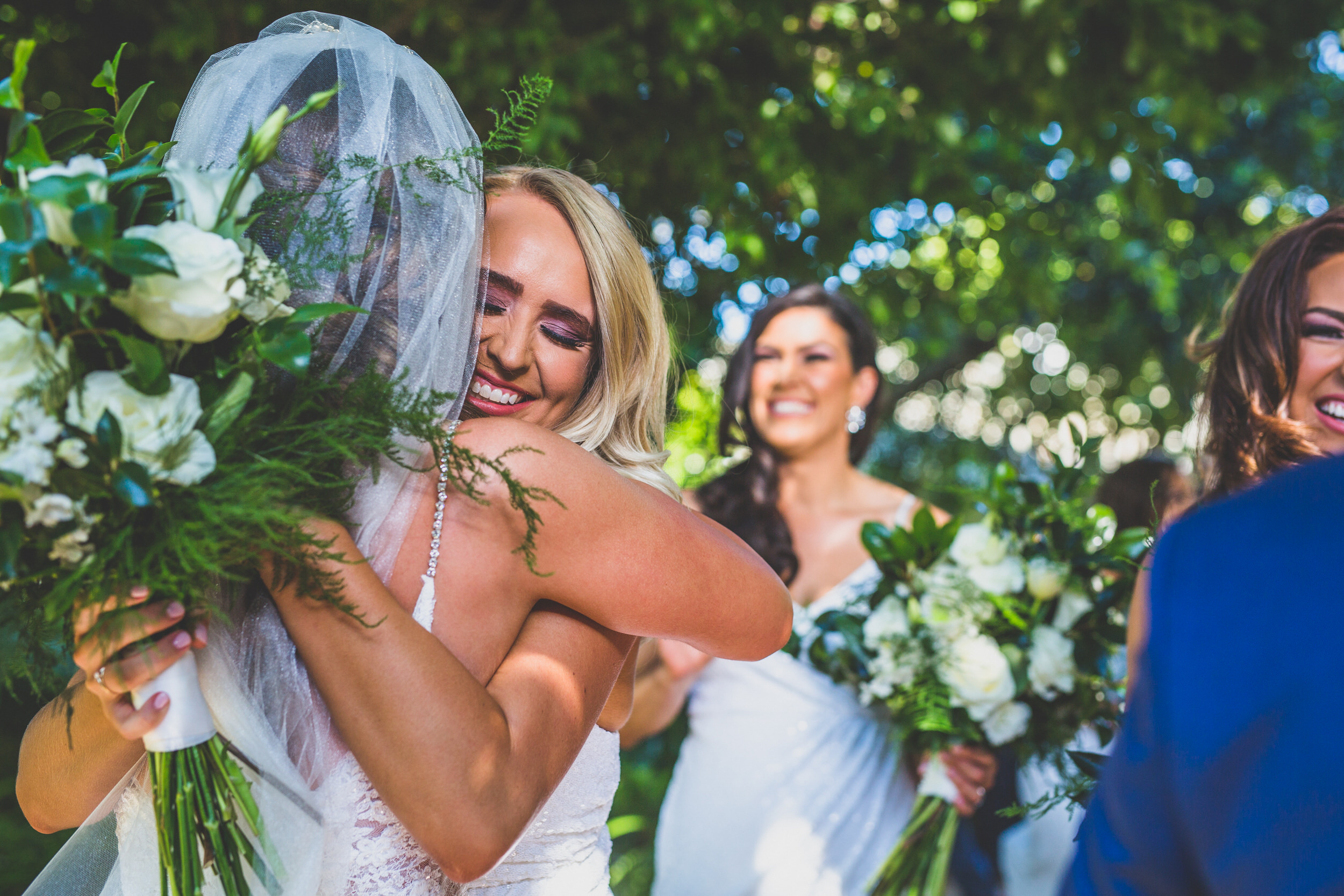 A bridesmaid congratulating her best friend, the bride.
