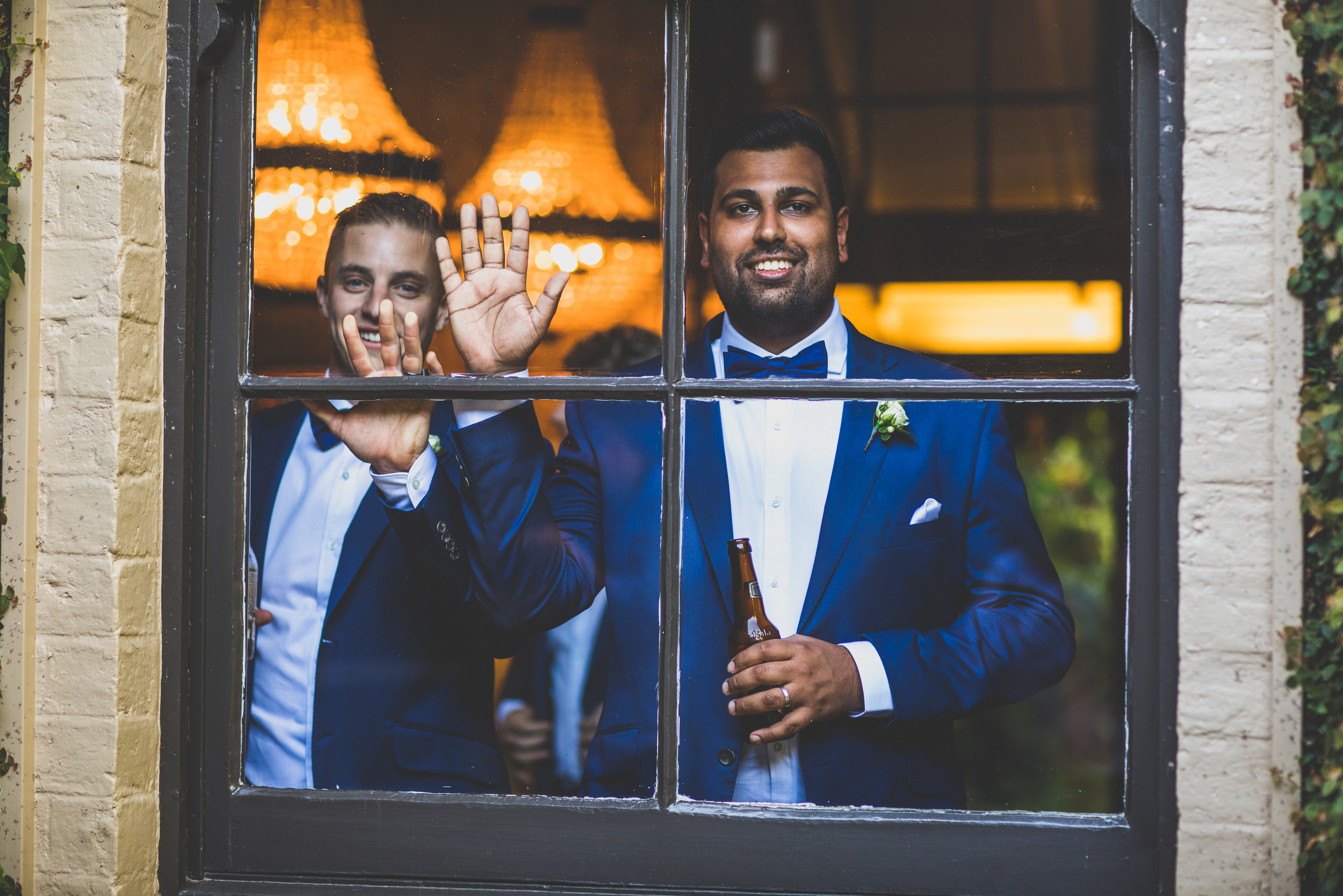 two groomsmen through a window