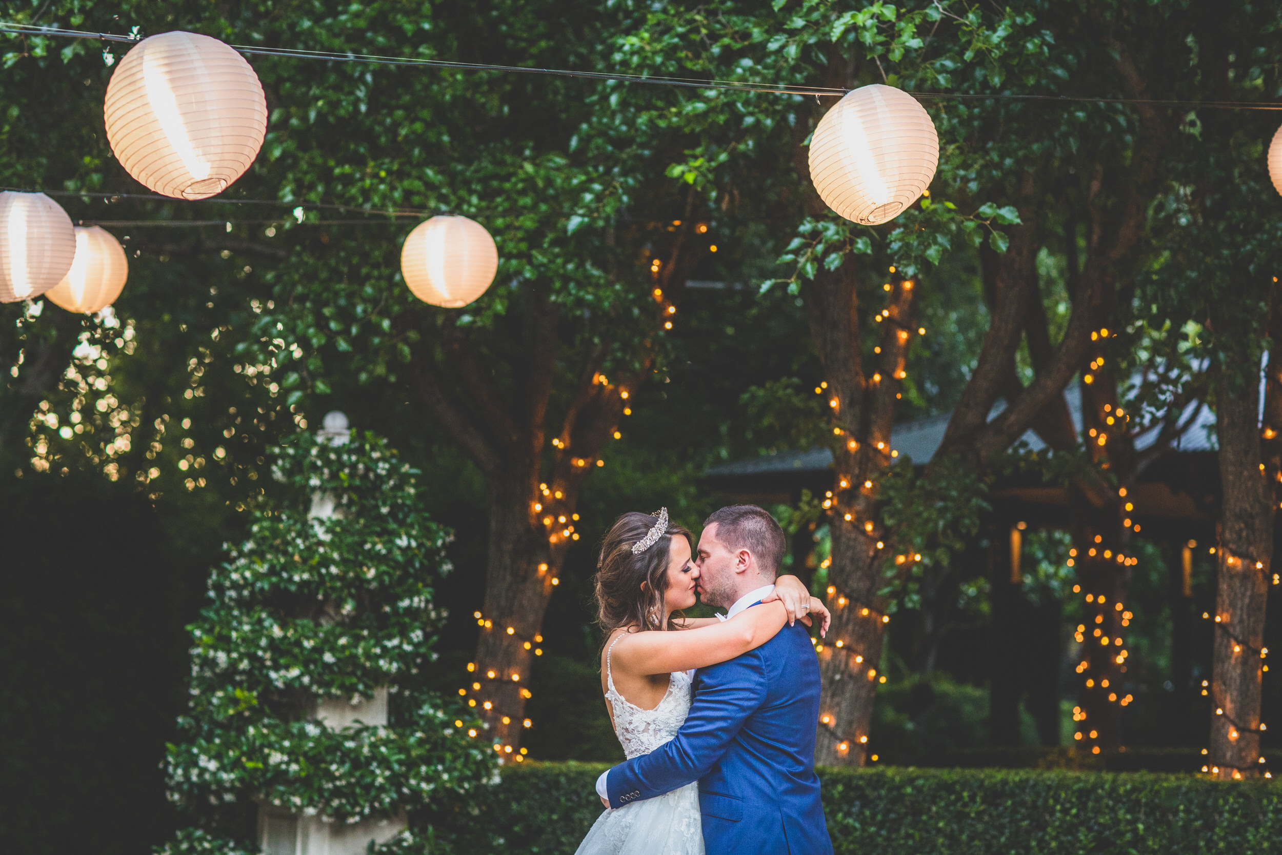 The bride and groom kissing under the lanterns, surrounded by fairy lights at Jaspers in Berry