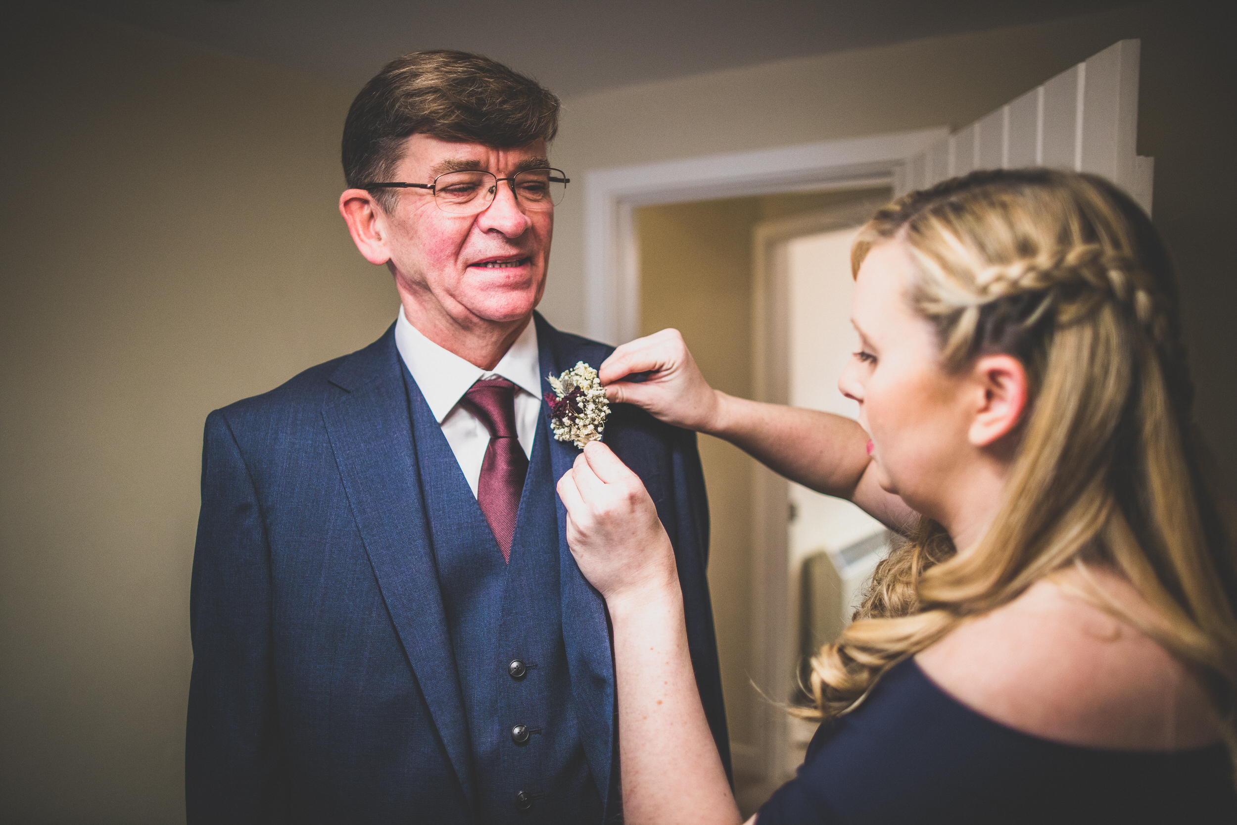 Putting the buttonhole on her father