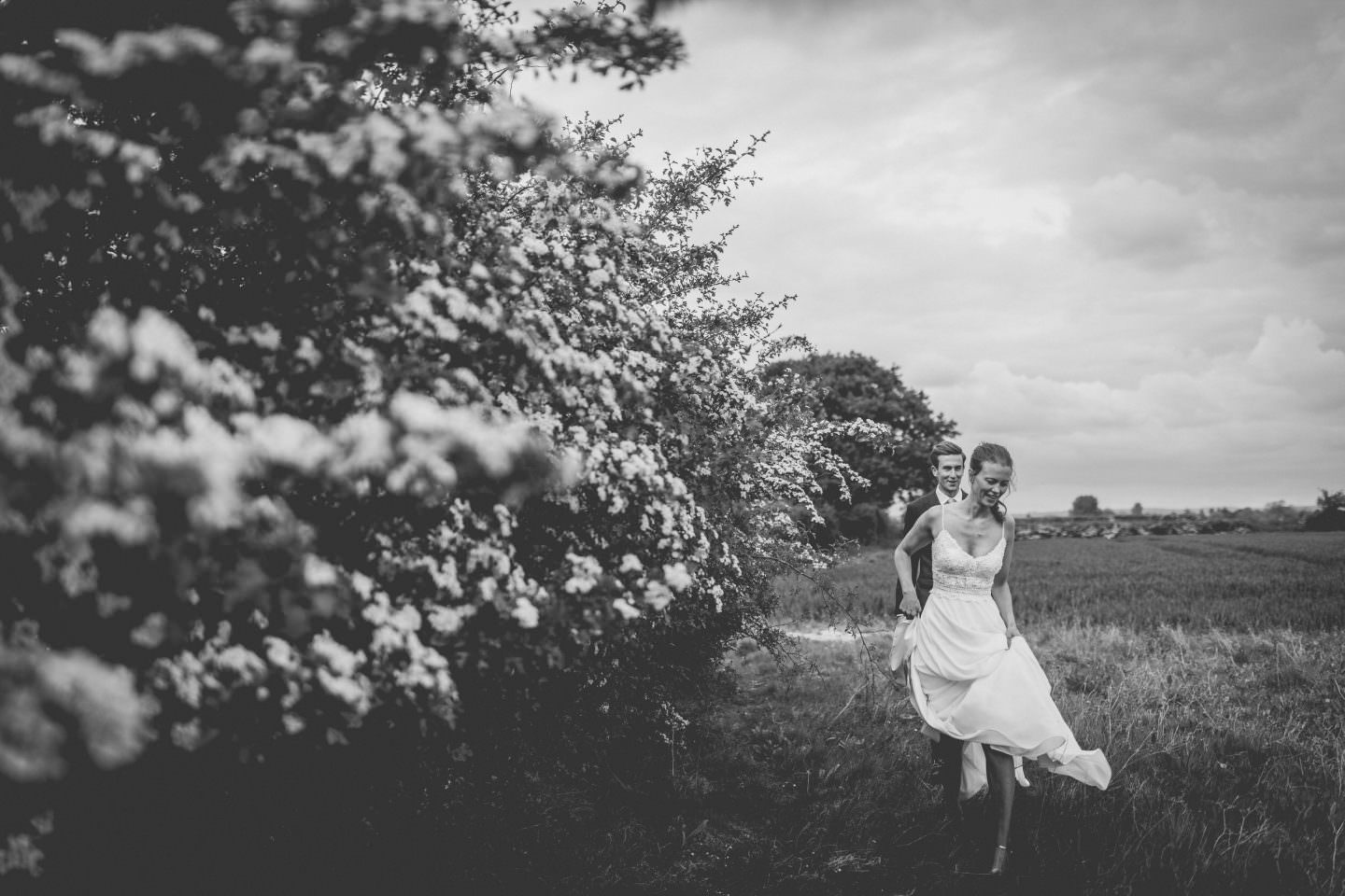 Bride and groom through a field