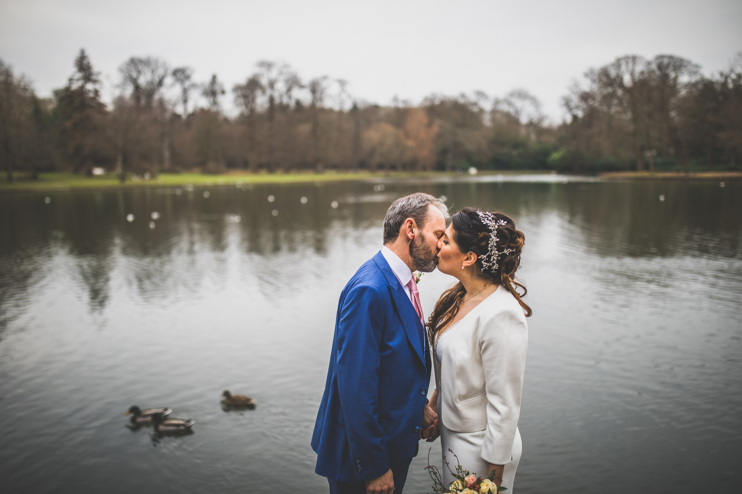the bride and groom sharing a kiss by the lake at Claremont Gardens