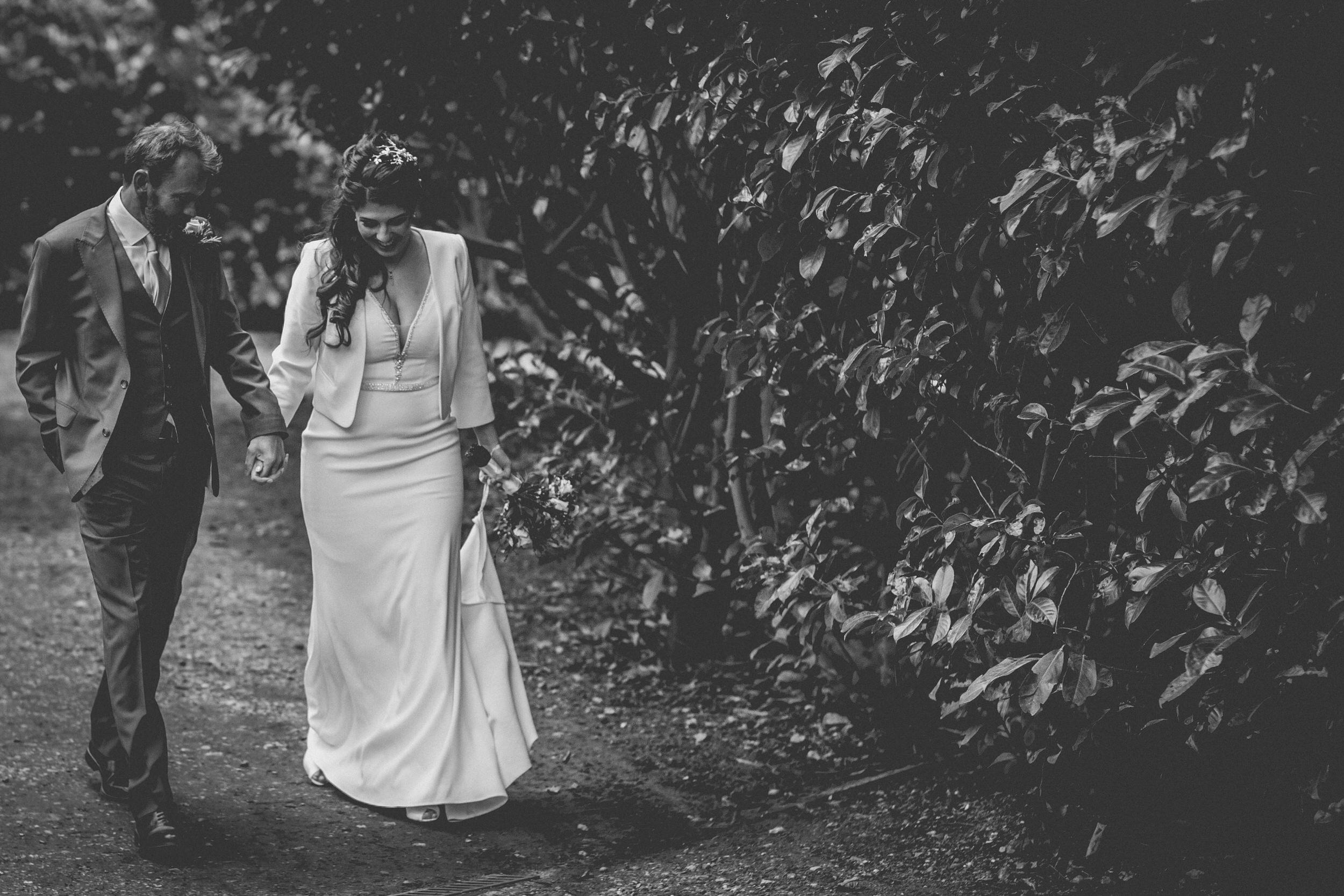 bride and groom walking through gardens