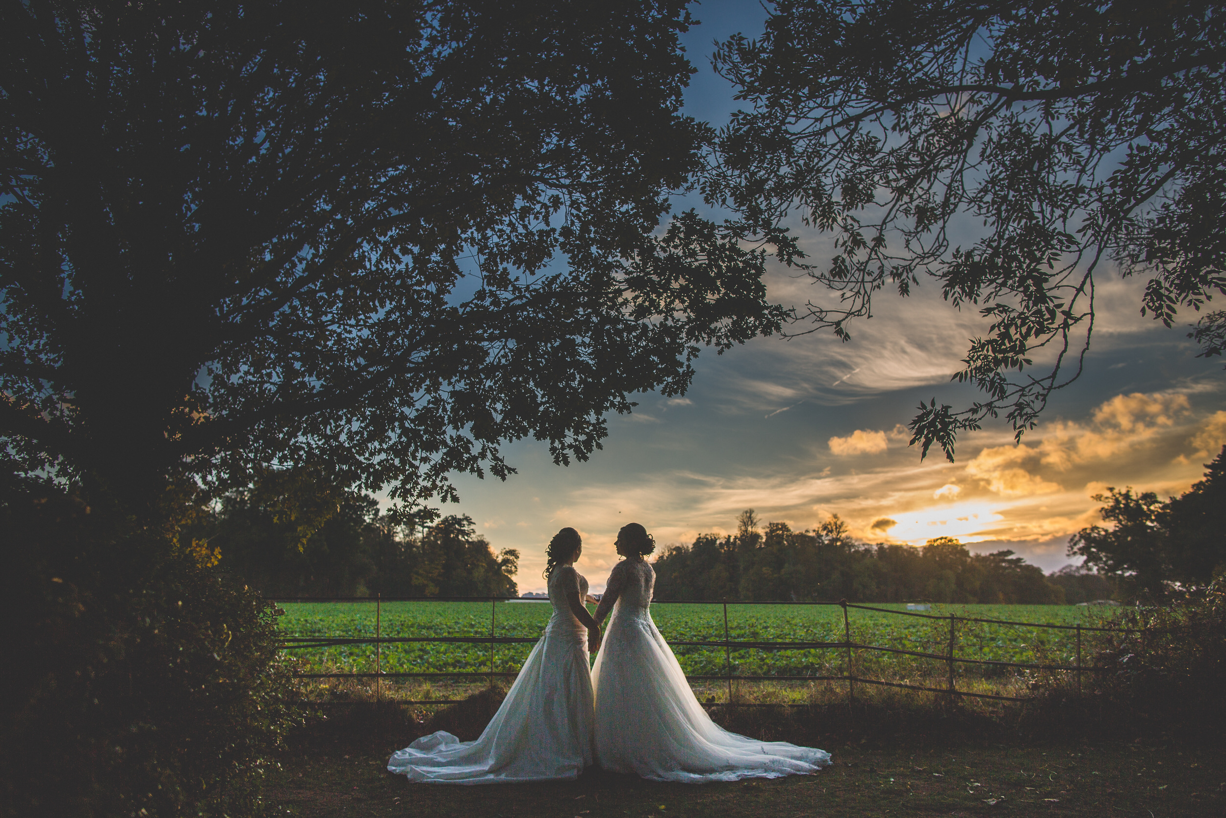 two brides getting married with the sunset