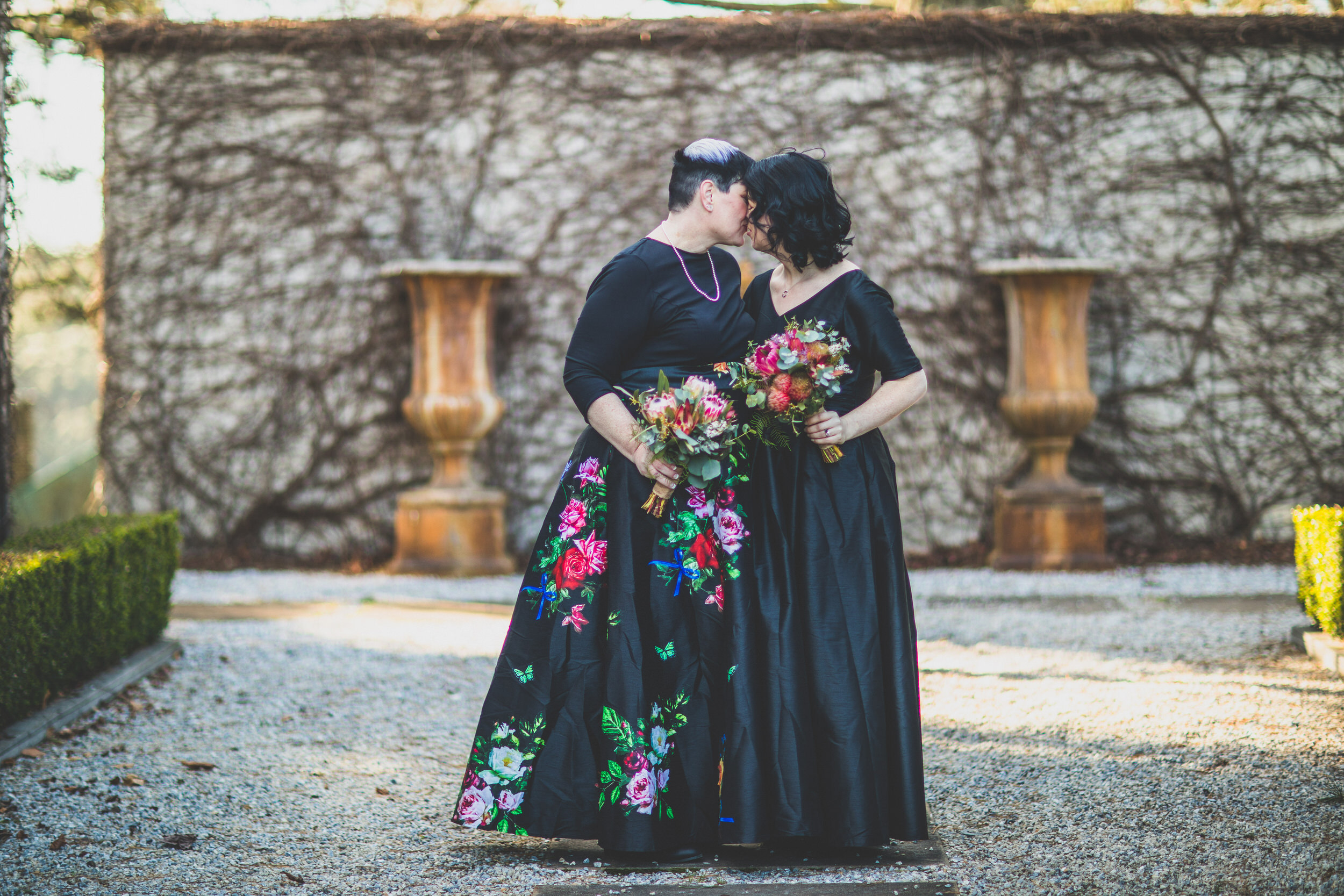 two women kissing in black wedding gowns